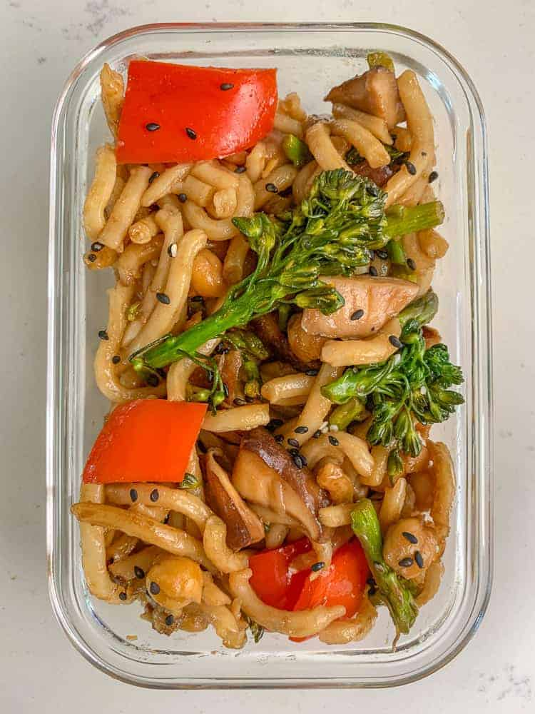 Food container filled with vegan stir fry noodles and vegetables