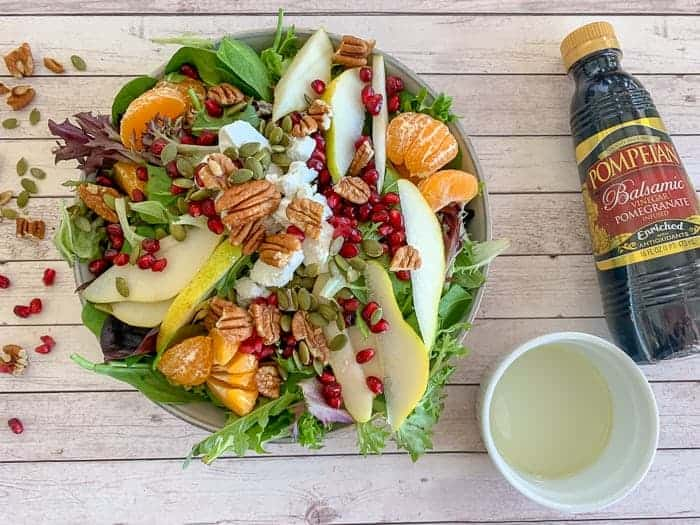 Pomegranate balsamic dressing over salad with pomegranate, pear, pecans, mandarins, and goat cheese