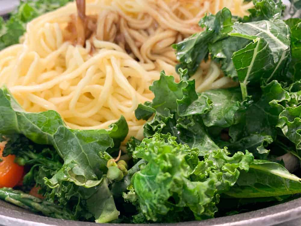 Add cooked noodles, greens and sauce to vegan stir fry