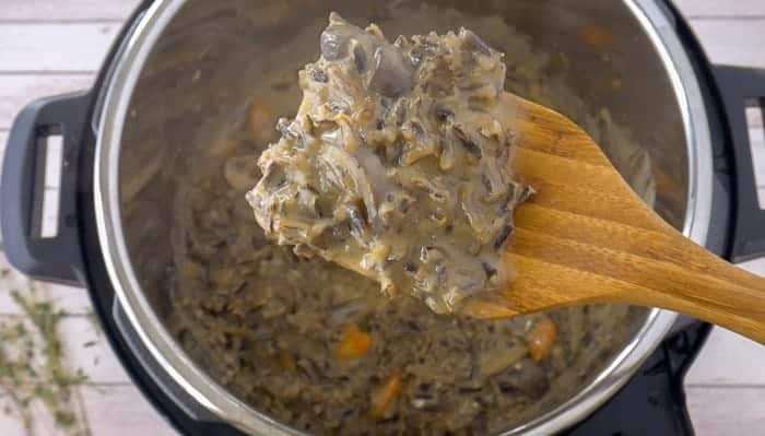 a wooden spoon stirring in a pot of vegetarian wild rice soup