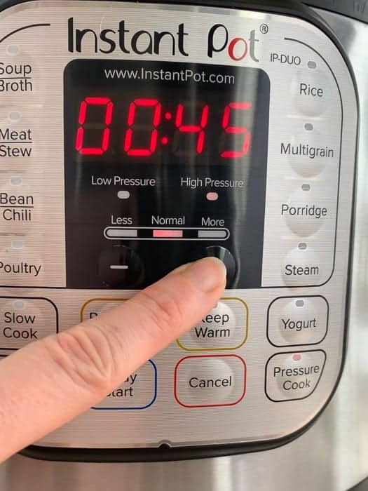 a finger pressing the Instant Pot Pressure Cooking Mode Button to make wild rice soup