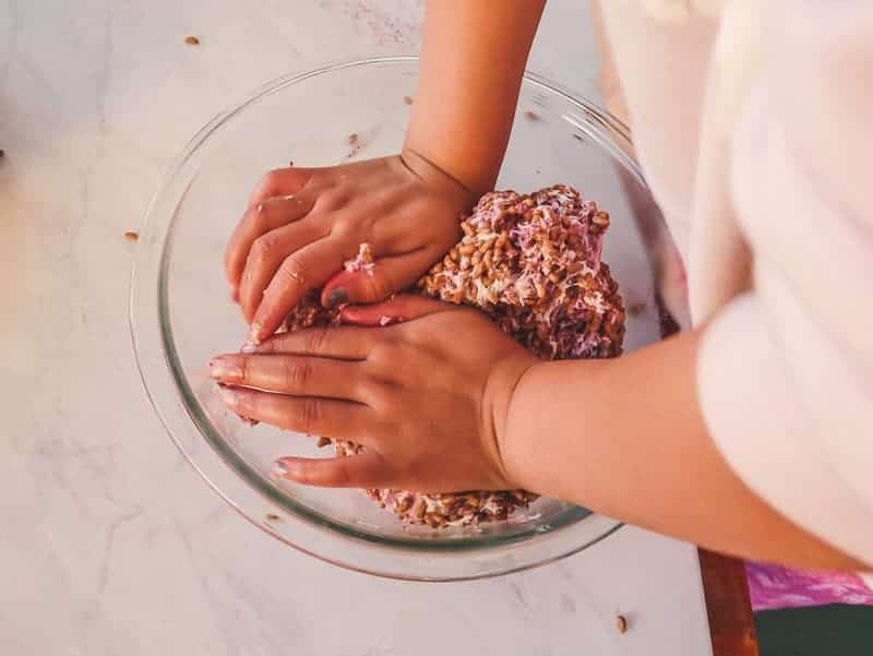 Wet hands make it easier to combine marshmallows and rice cereal for marshmallow treats