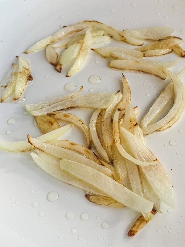 white onions being sauteed in a pan