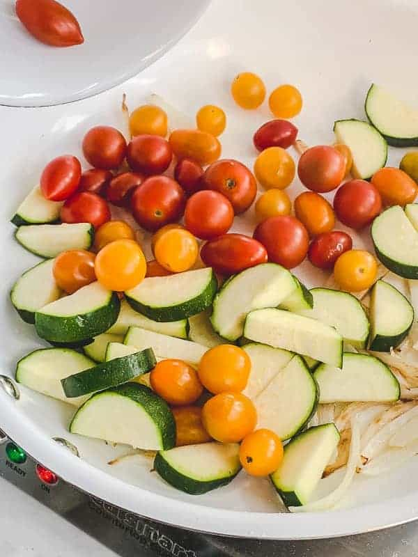 Onion, zucchini and baby tomatoes sauteeing in a pan