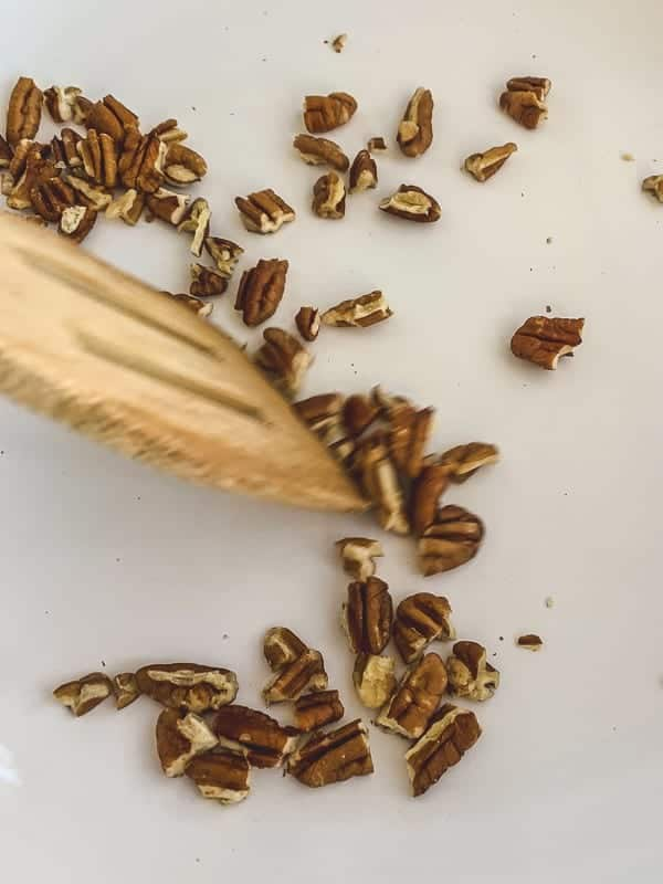 chopped pecans being toasted in a pan