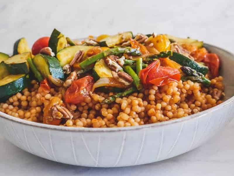 side view of a bowl of perfectly cooked toasted pearl couscous topped with balsamic vegetables