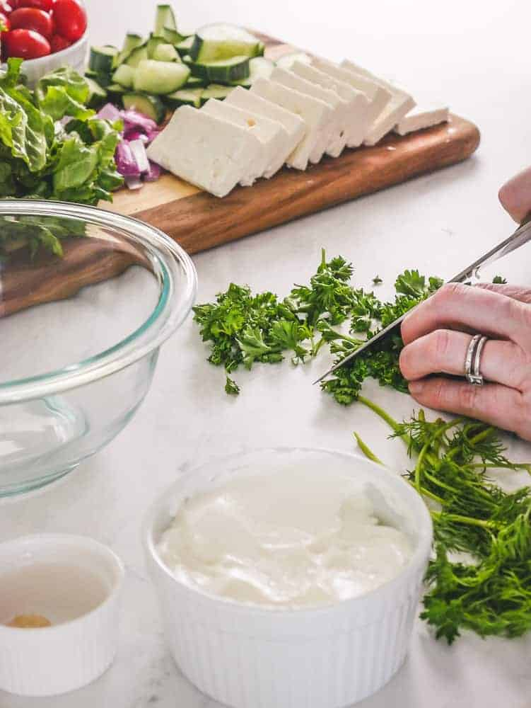 Chopping fresh parsley for Greek salad meal prep