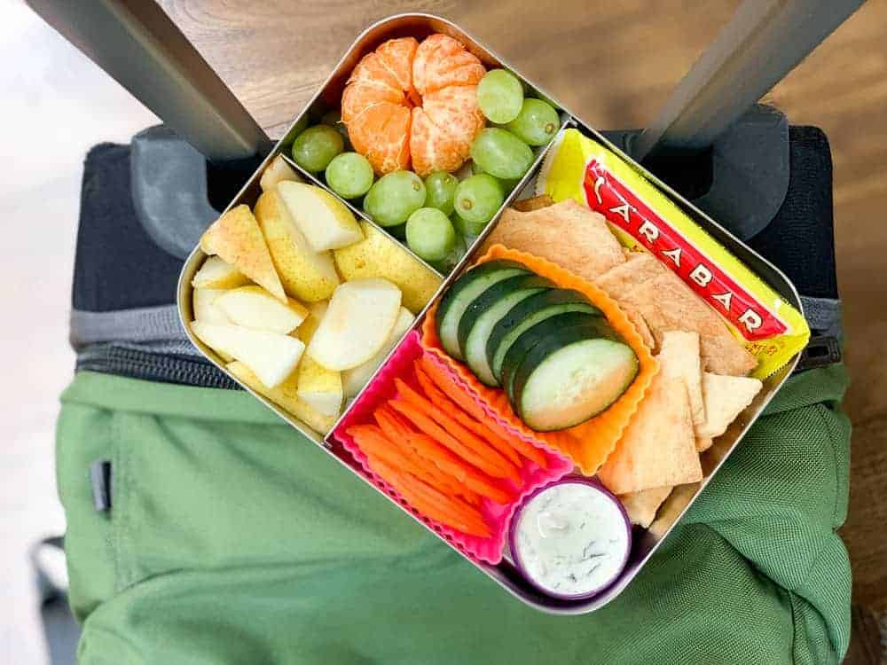 Food container with fresh fruit and vegetables sitting on top of a green suitcase