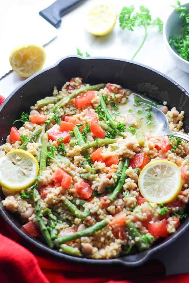 Cast iron skillet filled with millet rice, asparagus and tomatoes