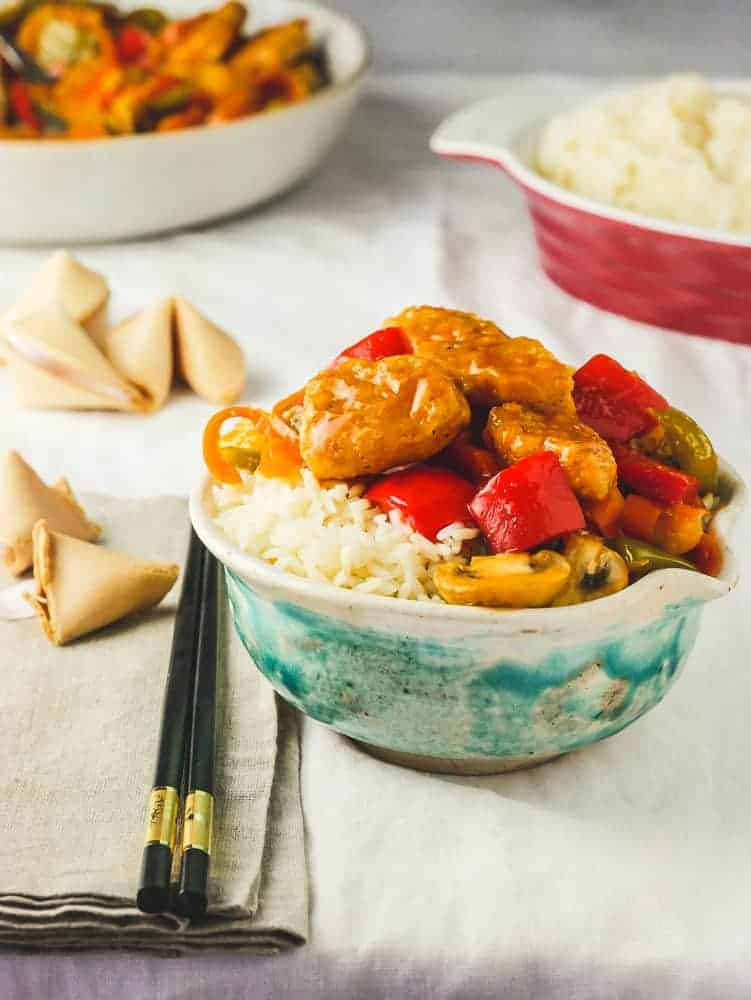 Bowl with rice and vegan chicken with vegetables, chopsticks and fortune cookies on the side