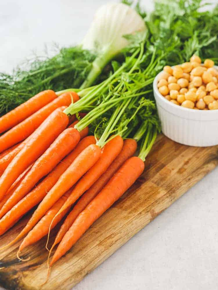 Carrots, chickpeas and fennel on a wooden chopping board