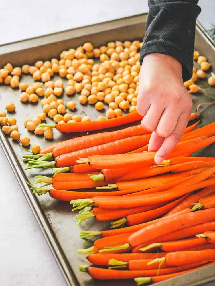 a child's hand sneaking a carrot from a sheet pan