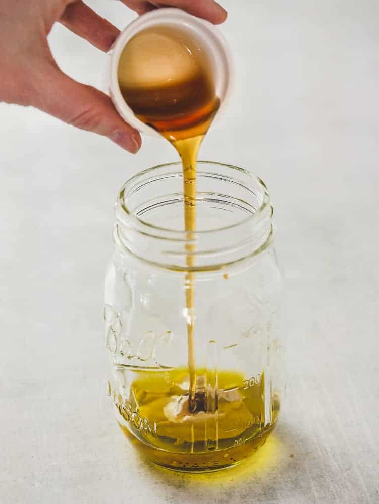 ingredients for maple dijon dressing being poured into a mason jar