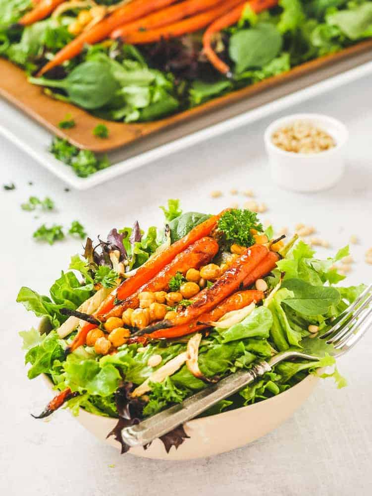 leafy greens topped with roasted carrots, fennel and chickpeas in a salad bowl