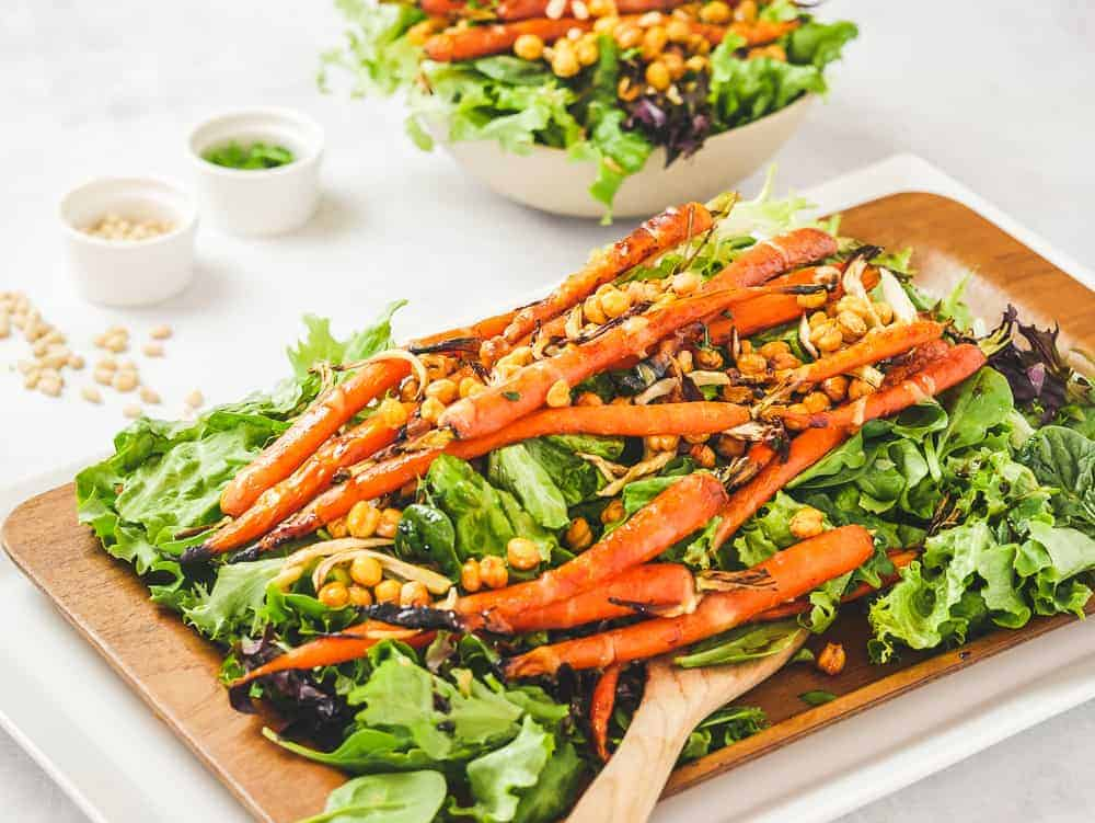 Warm Roasted Vegetable Salad with carrots, fennel and chickpeas on a wooden board