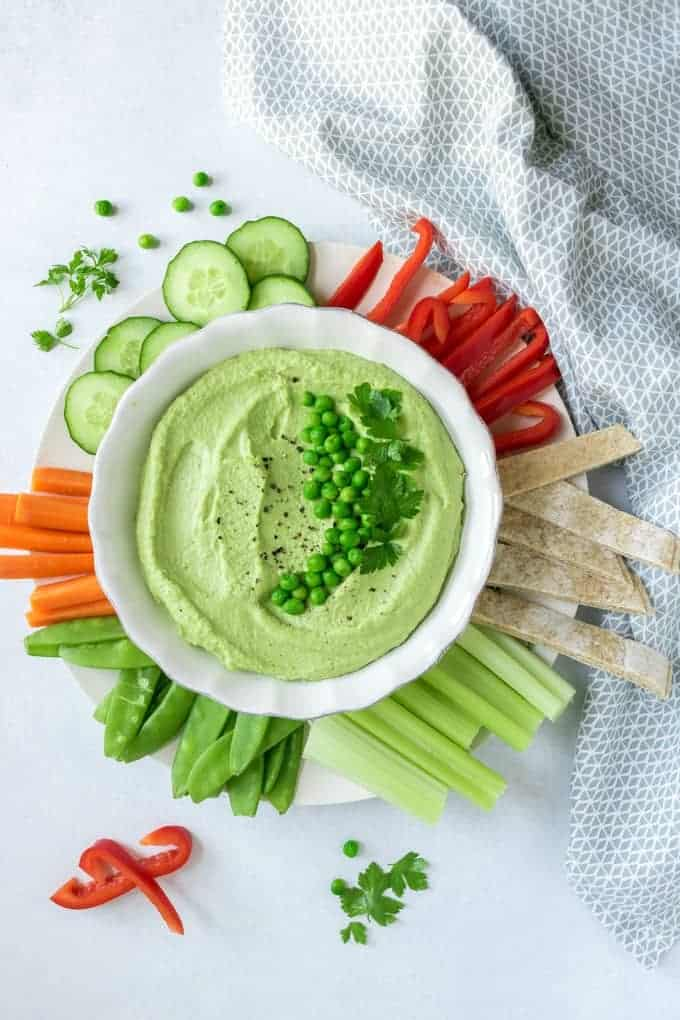 Bright green pea hummus topped with spring peas, surrounded by raw vegetables