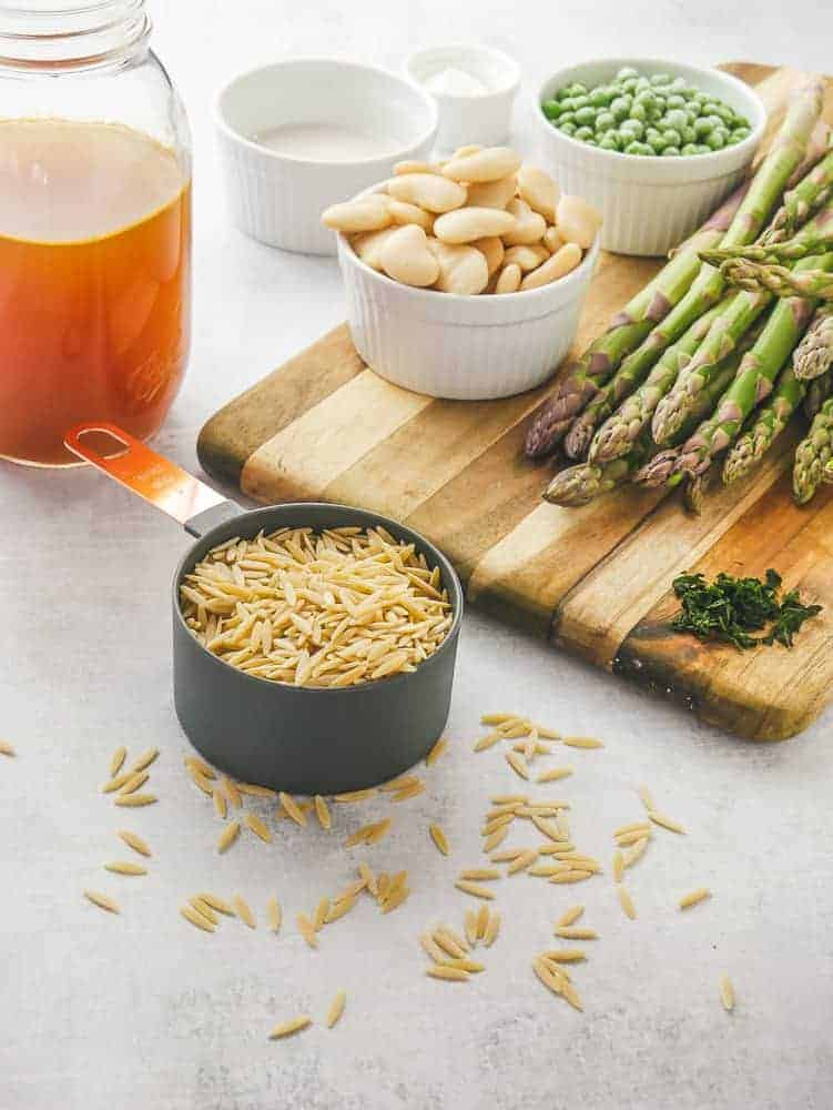 Wooden cutting board with asparagus, butter beans, peas and basil on it. Surrounded by orzo, broth and small bowls of ingredients.