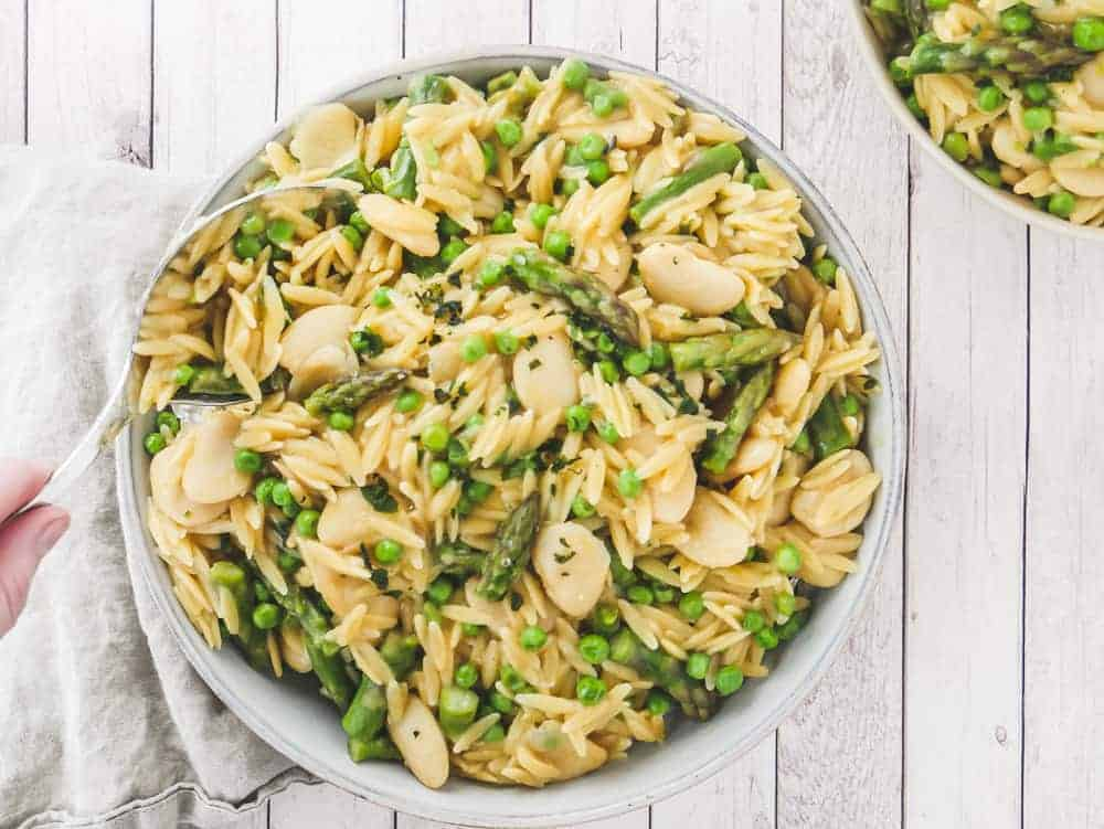Hand scooping a spoon into creamy vegan orzo pasta dish with asparagus, peas and butter beans