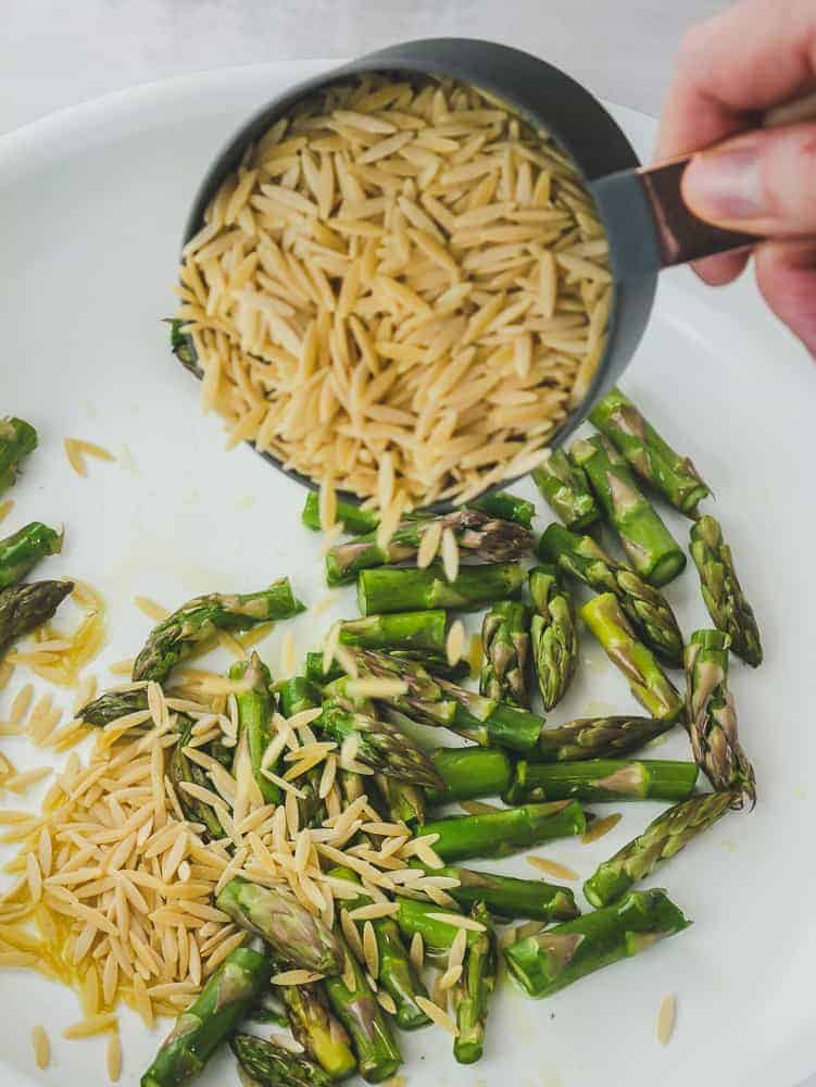 Measuring cup pouring raw orzo pasta into a white pan with asparagus