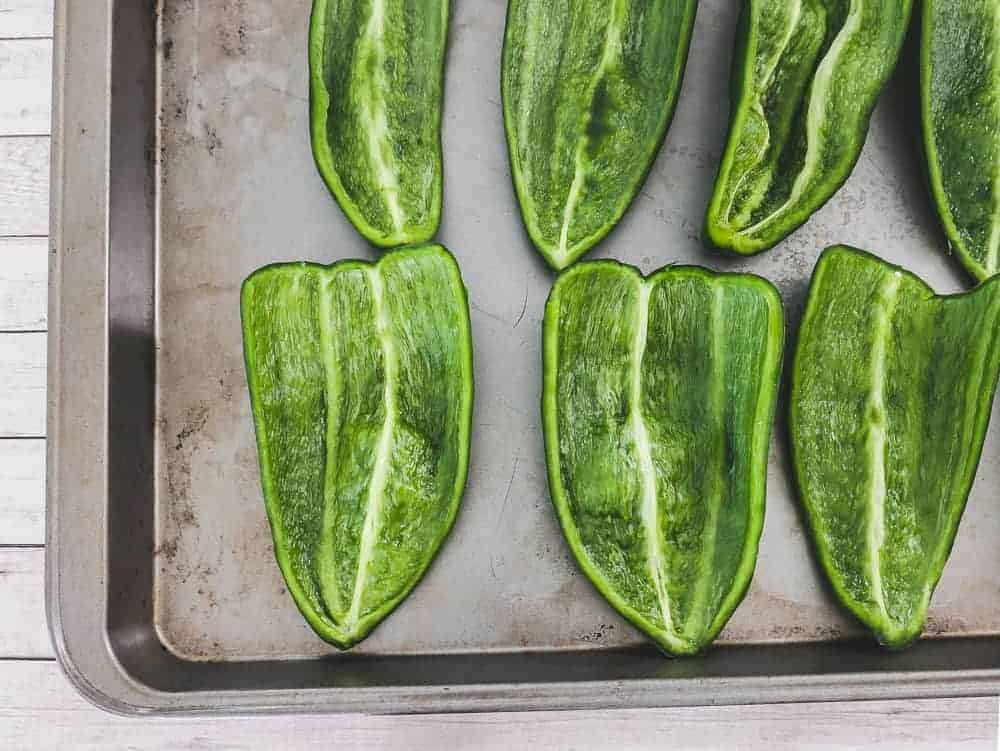 poblano peppers being deseeded on a cutting board