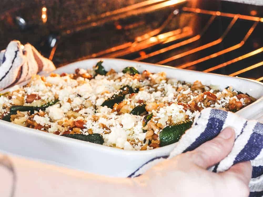 a casserole dish with vegetarian chile rellenos going in the oven