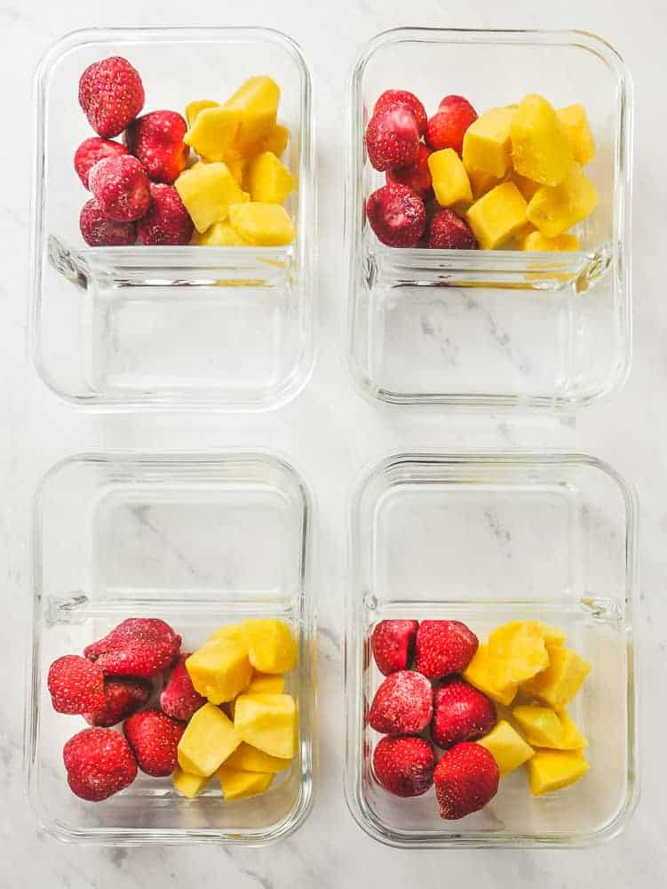 4 food storage containers, each with portions of strawberry and mango