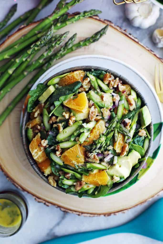 Bowl with a salad of asparagus, orange, spinach and nuts