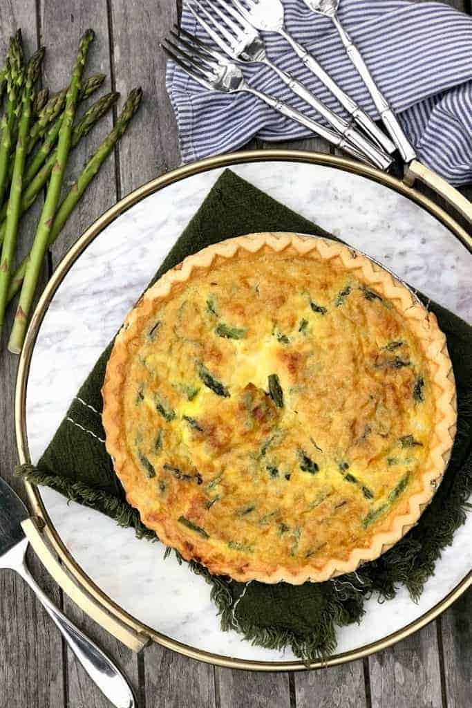 Round quiche on a plat with small pieces of asparagus visible