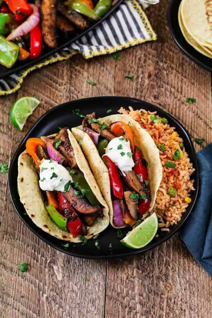 Two fajita tacos on a plate, filled with sliced peppers and portobello mushrooms