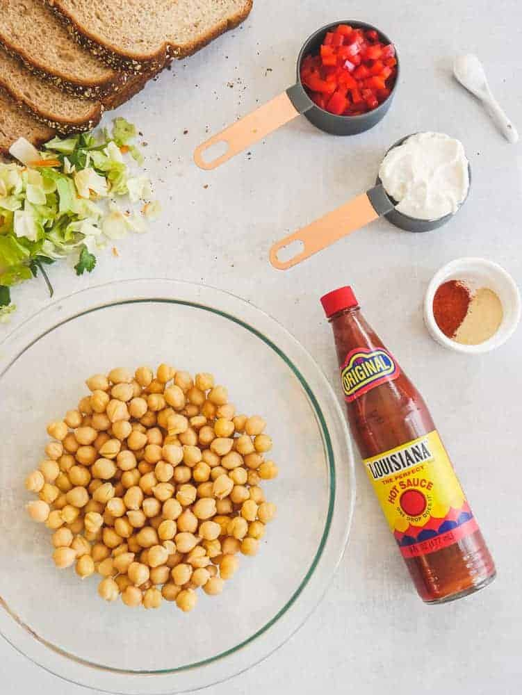Ingredients to make buffalo chickpea salad on the counter in bowls