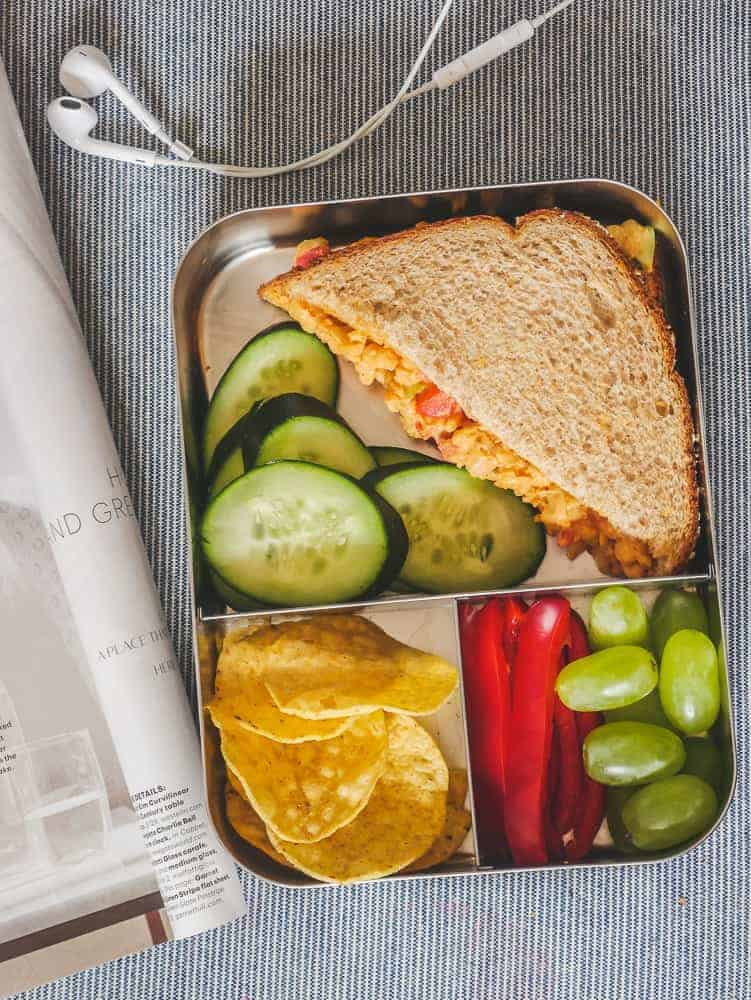 Lunch box with sandwich, raw fruits and veggies, on an airplane seat with headphones and magazine