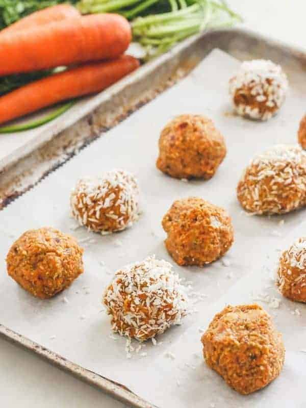 Carrot cake balls, some with coconut shreds, in a pan. Carrots in the background.