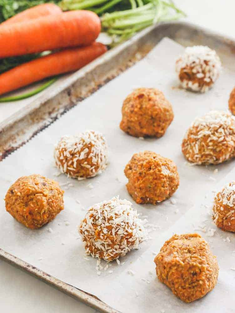 Carrot cake bliss balls, some with coconut shreds, in a pan. Carrots in the background.