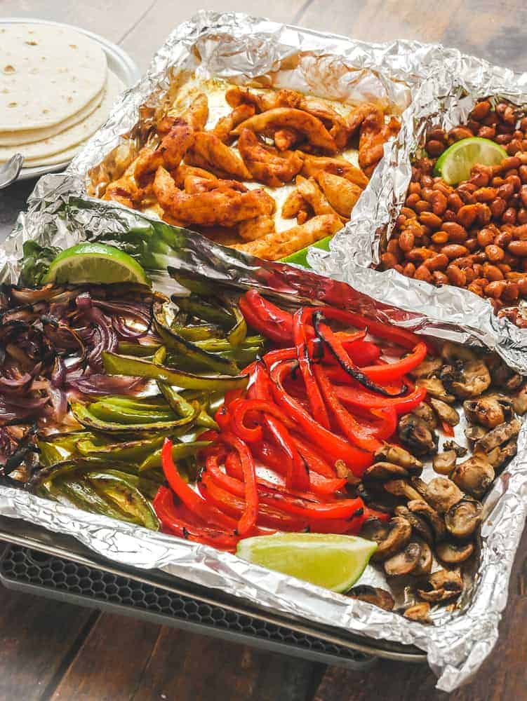Baking sheet lined with foil, with sections of vegetables, peppers and chicken.