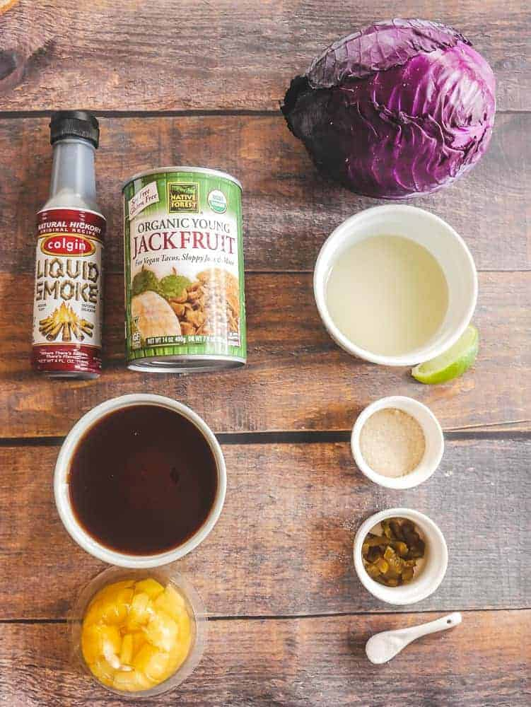 BBQ Jackfruit Sandwich ingredients: can of jackfruit, liquid smoke, purple cabbage and small white cups of various ingredients