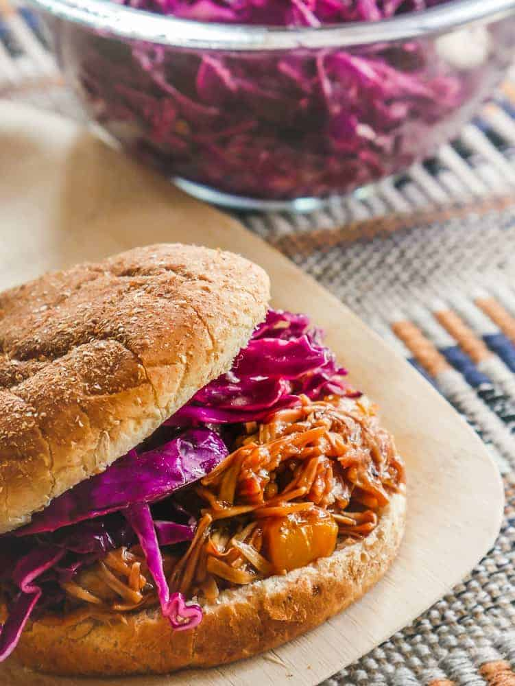 jackfruit with purple cabbage coleslaw between whole wheat buns, bowl of coleslaw in the background