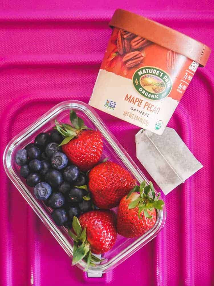An oatmeal cup, tea bag and mixed berries sitting on top of a pink suitcase. Vegan breakfast for airplane and vegan travel snacks.