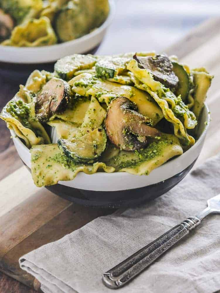 Bowl filled with vegan pesto handkerchief pasta, fork in the foreground