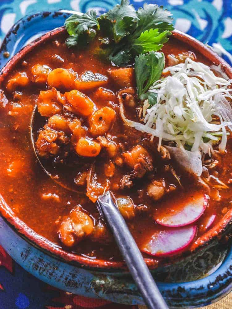 Slow cooker vegan pozole in a blue bowl, spoon filled with red sauce covered hominy and soy chorizo.