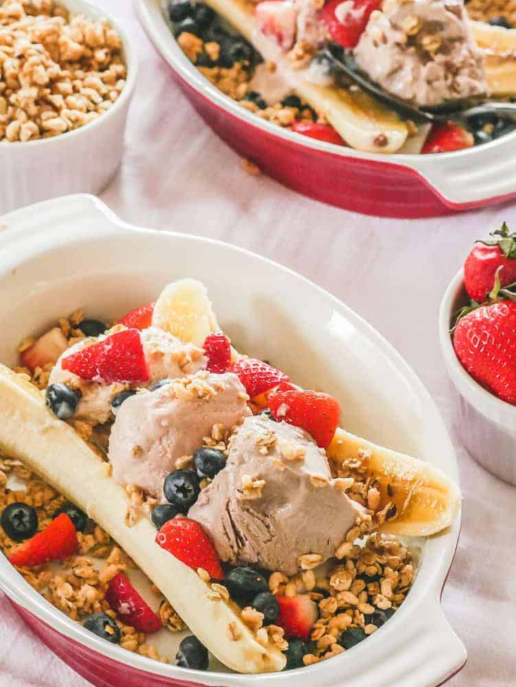 Red bowl with a vegan banana split. Bananas topped with frozen yogurt, granola and berries.