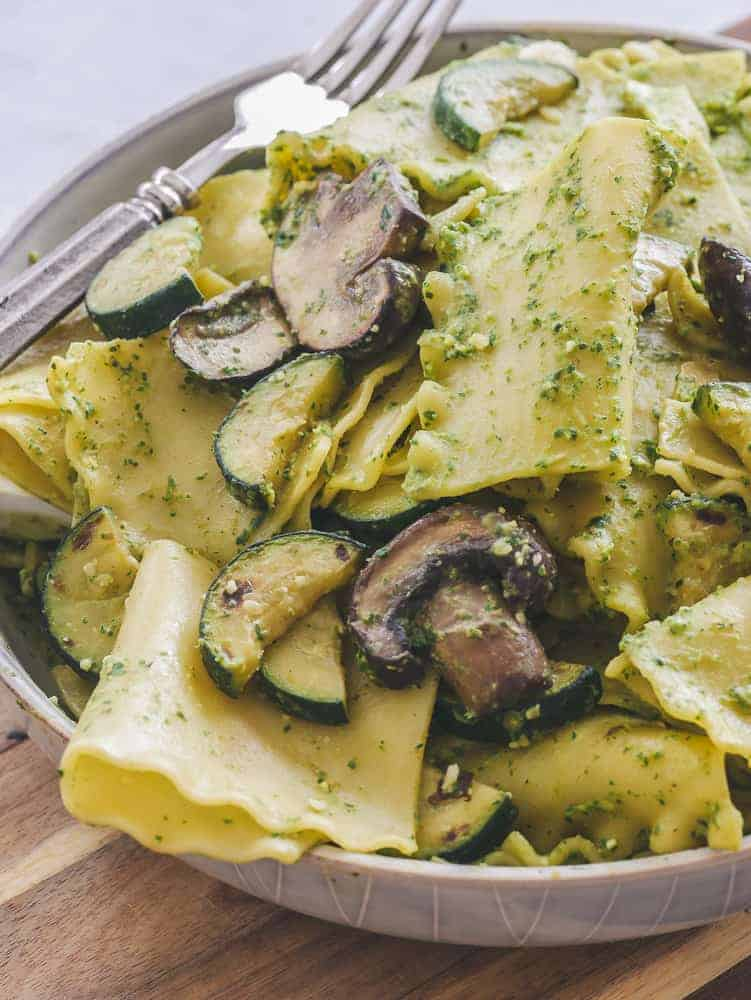 Bowl of mandilli di seta (handkerchief pasta) topped with mushrooms, zucchini and vegan pesto