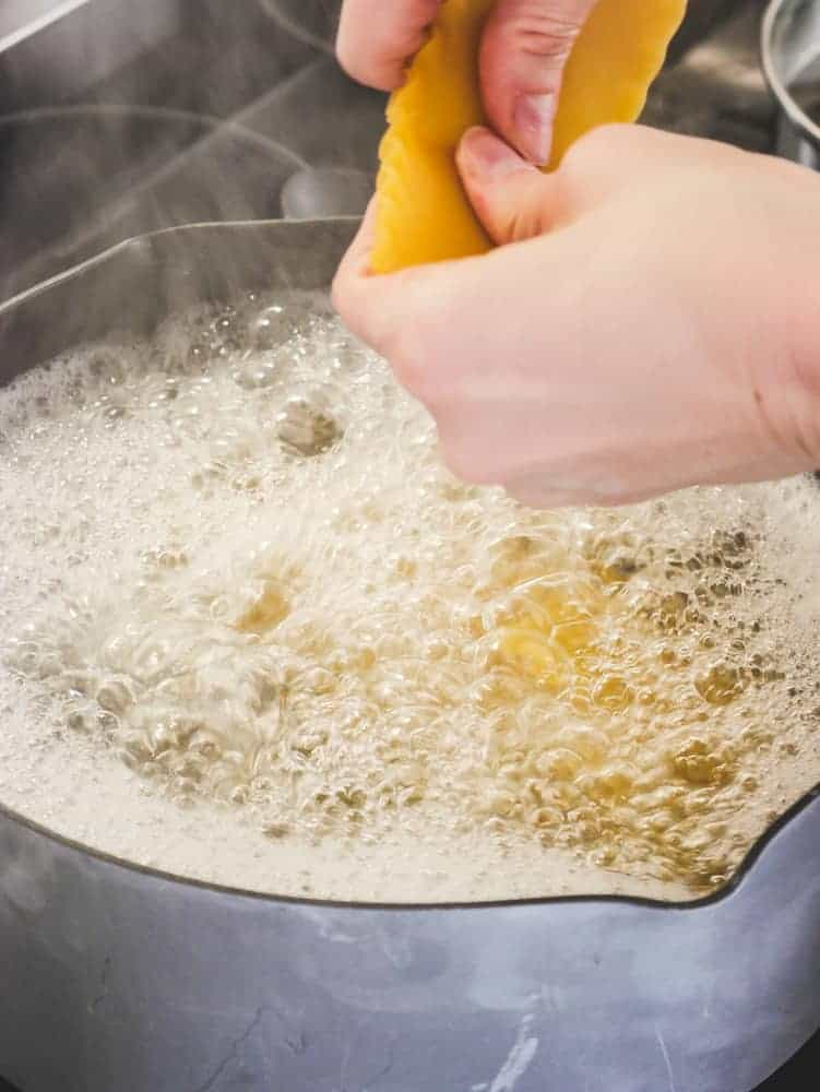 Hands breaking lasagna into boiling water