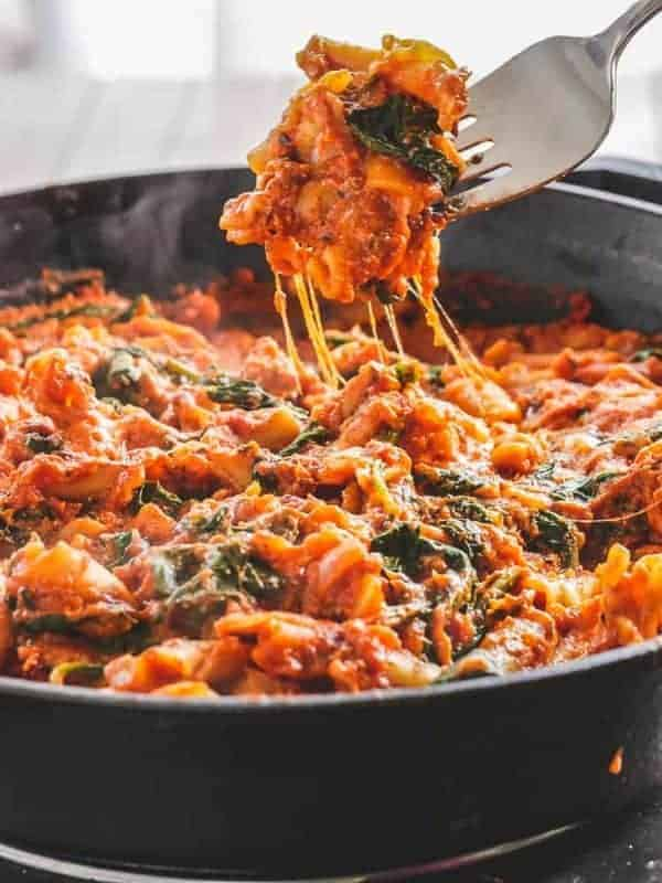 Fork lifting a bite of pasta and spinach from a cast iron skillet
