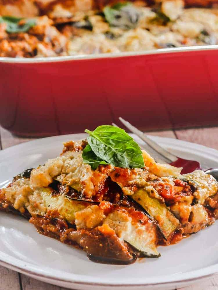 Plate with a slice of vegan eggplant zucchini lasagna topped with basil, red dish of lasagna in the background