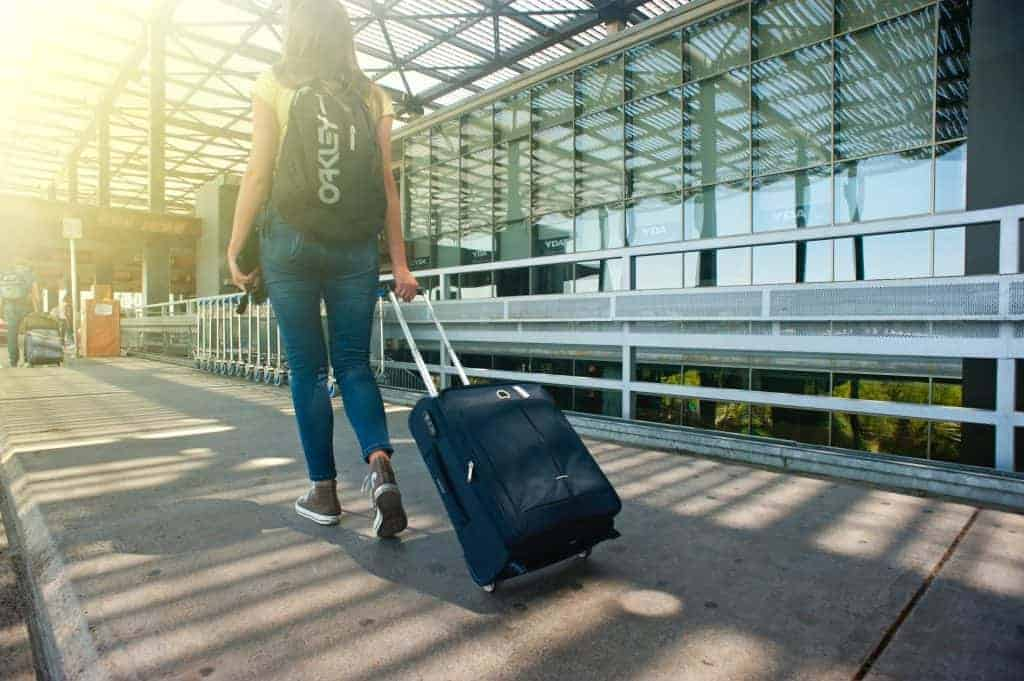 Young woman traveling, and pulling a suitcase in front of an airport