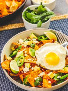 Easy Chilaquiles with Eggs in a ceramic bowl, with a fried egg on top, and a fork resting in the bowl.