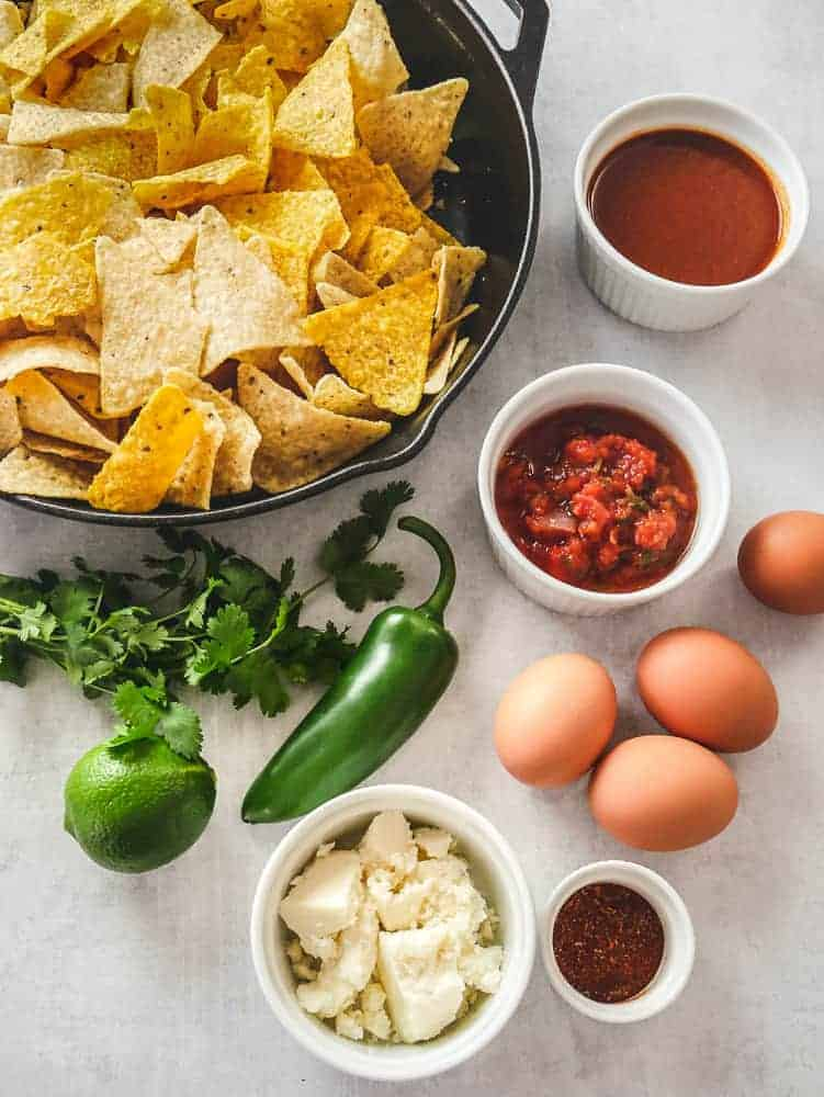 Ingredients for chilaquiles: tortilla chips in a cast iron skillet, eggs, jalapeno, tomato sauces and other ingredients