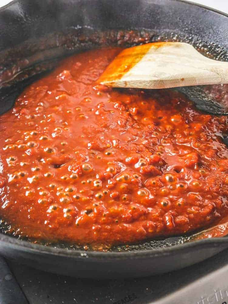 Bubbling salsa and enchilada sauce in a skillet