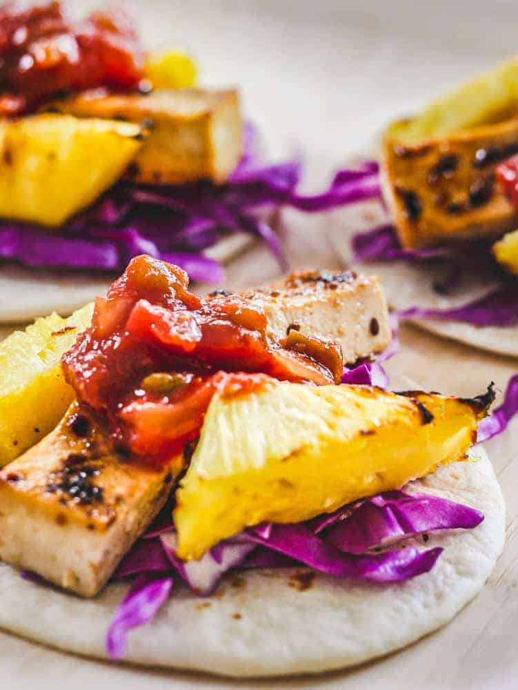 White plate with small street vegan tacos with grilled pineapple chunks