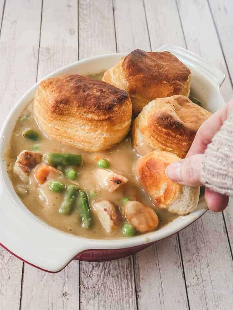 Hand dipping biscuit into a dish of pot pie
